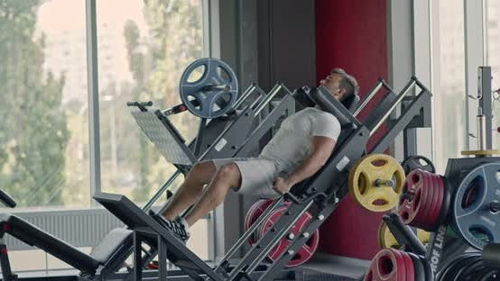 Thumbnail for Hard Bodybuilding Workout. Concentrated Man Exercising on Squat Training Machine at Gym