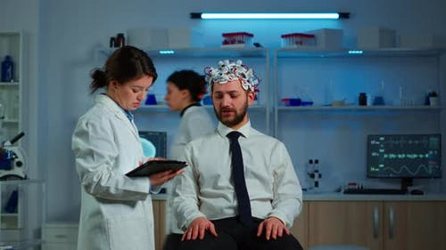 Patient Wearing Brainwave Scanning Headset Discussing with Neurological Researcher