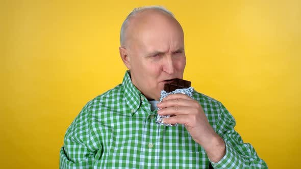 Thumbnail for Elderly Man Biting Chocolate Bar