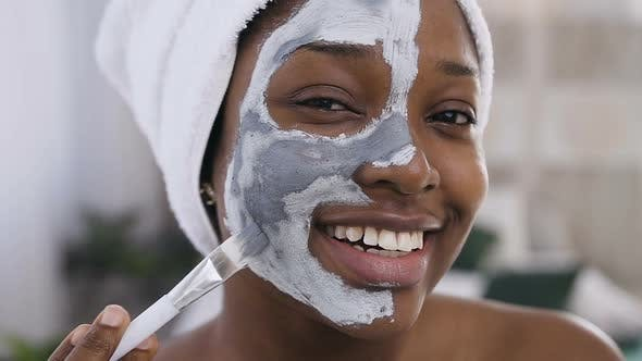 Thumbnail for Smiling Afro-American Girl with Towel on the Head Applying a Cleansing Clay Mask on Face