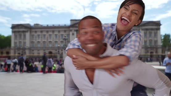 Thumbnail for African-American man playfully carrying girlfriend on back at Buckingham Palace