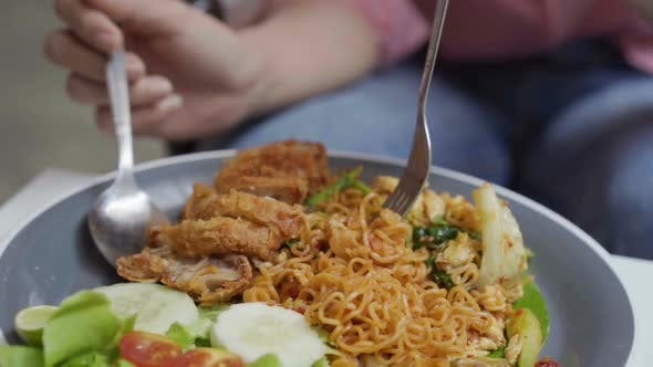 slow-motion of hand using fork for eating instant noodle