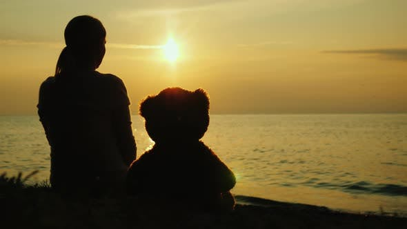 Cover Image for A Lonely Woman with a Toy Bear Looks at the Sunset Over the Sea