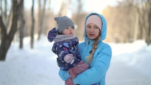 Mutter und Tochter gehen im Winter zusammen Hand in Hand