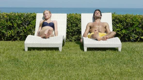 Thumbnail for Young couple sleeping on sun loungers