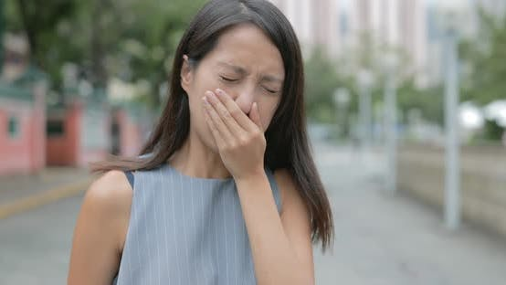 Woman feeling nose allergy in city