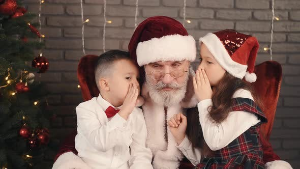 Girl and Boy Whispering Wishes To Santa