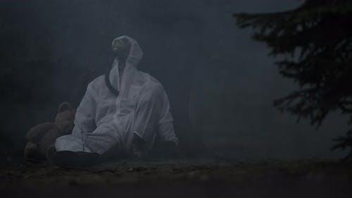 Hoffnungslose Männer tragen chemische Gasmaske Sitz neben Teddybär im verschmutzten Wald