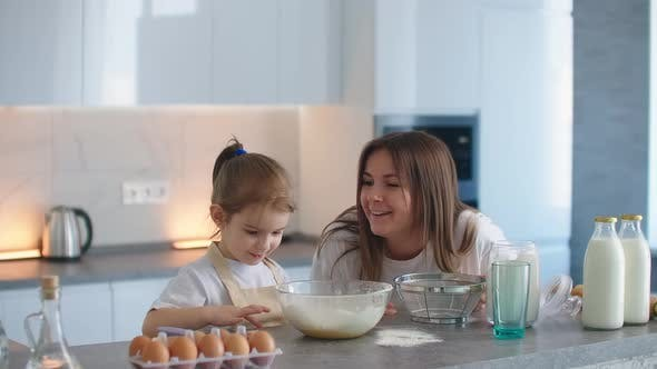 Thumbnail for Mom and Daughter Indulge and Play Pranks in the Kitchen, Daughter Using Flour Smeared Mom's Nose and