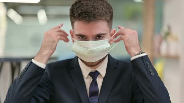 Thumbnail for Cautious Young Businessman Wearing Protective Face Mask
