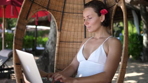 Digital Nomad Concept  White Female Working on Her Laptop From a Beach