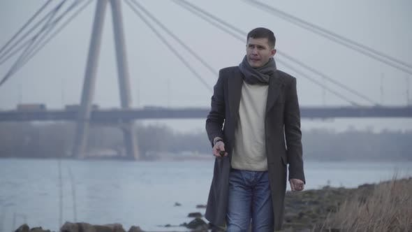 Cover Image for Middle Shot of Depressed Caucasian Man in Elegant Coat and Scarf Walking on Riverbank and Throwing