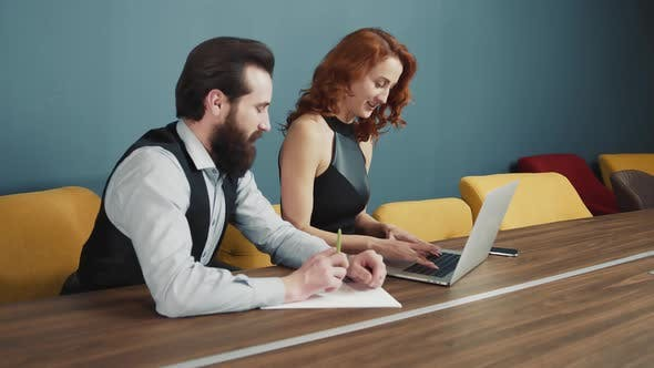 Woman Typing Text on a Laptop in the Office and Next To a Man with a Beard Writing Text