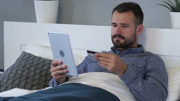 Cover Image for Online Shopping on Tablet by Tired Man in Bed