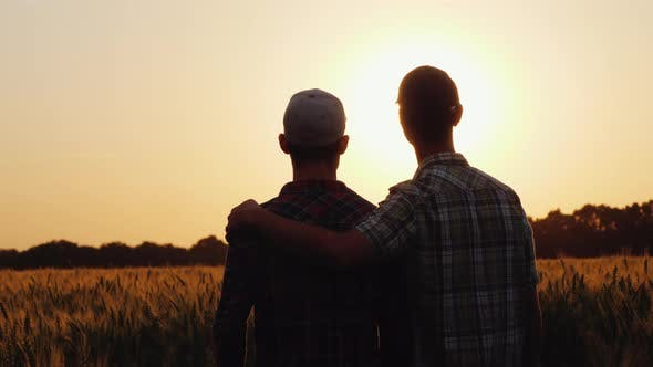 Thumbnail for Two Men Gently Cuddle, Look Forward To the Boundless Field of Wheat
