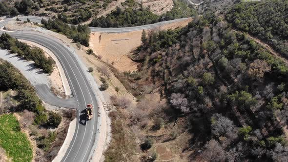Truck with excavator is passing mountain pass.