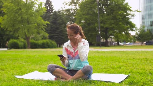 Woman with Smartphone Putting Music for Meditation 75
