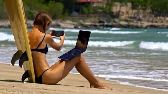 Girl Leans on Surfboard Takes Photos on Sand Beach