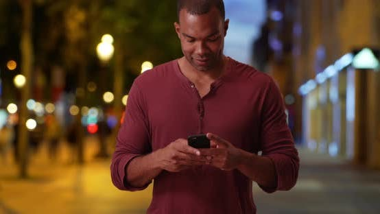 Thumbnail for Casual African man on Champs-Elysees sends text message on evening out