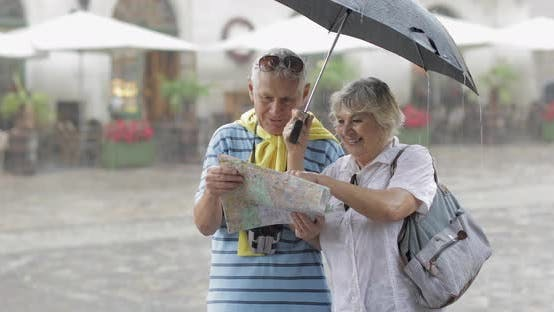 Senior Tourists in Rainy Weather Stand and Looking for the Route in Map