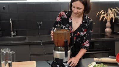 Woman mixing ingredients in blender. Female turning on blender, cooking tomato smoothie in kitchen