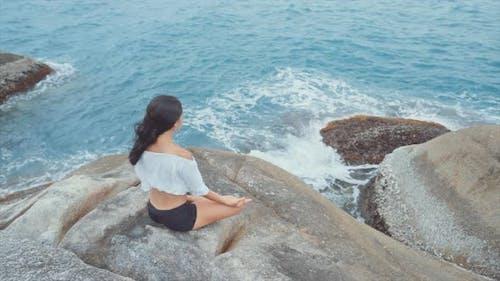 Frau sitzt am Ozean und Meditieren Hochwinkel