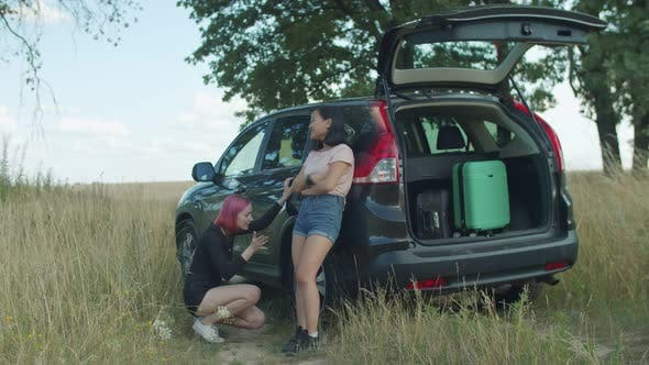 Thumbnail for Female Travelers Checking Out Flat Tyre on Car