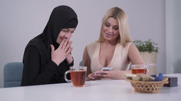 Thumbnail for Schüchtern muslimische Frau und zuversichtlich kaukasische Dame Blick auf Smartphone-Bildschirm und Lächeln