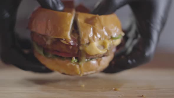Thumbnail for Hands of the Chef in Black Rubber Gloves Pressing Halves of Burger and Sauce Flowing Out