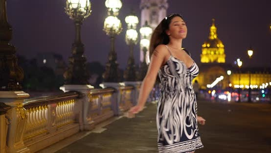 Thumbnail for Portrait of happy young carefree Latina woman twirling on a bridge in Paris