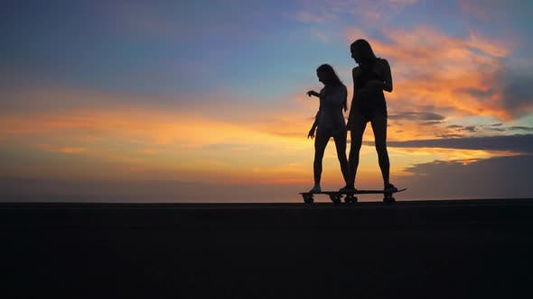 Thumbnail for Two Girlfriend Girls in Shorts and Sneakers Ride Skateboards on the Slope Against the Beautiful Sky