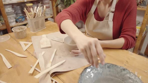 Thumbnail for Young Female Crafter Smoothing Walls of Clay Bowl with Moist Hand