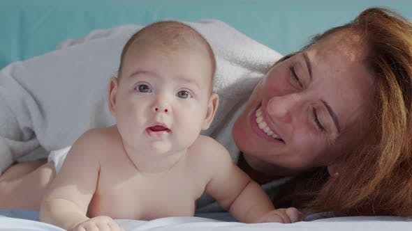 Happy Mother and Her Newborn Baby. Resting in Bed Together. Maternity Concept. Parenthood