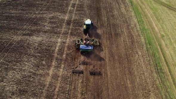 Aerial top view, drone fly forward follow tractor.