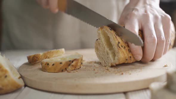 Slicing Baguette with Black Sesame Seeds on Table. Baguette Traditional French Bread on the Table