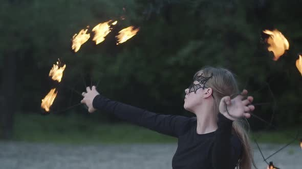 Thumbnail for Portrait of Young Beautiful Woman in Mask Performing a Show with Flame in Front of Trees
