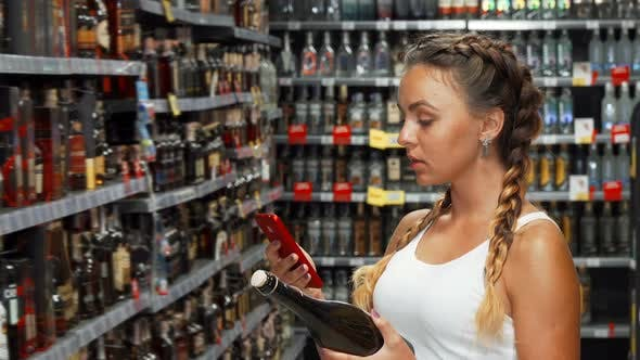 Woman Using Smart Phone at the Winery Store