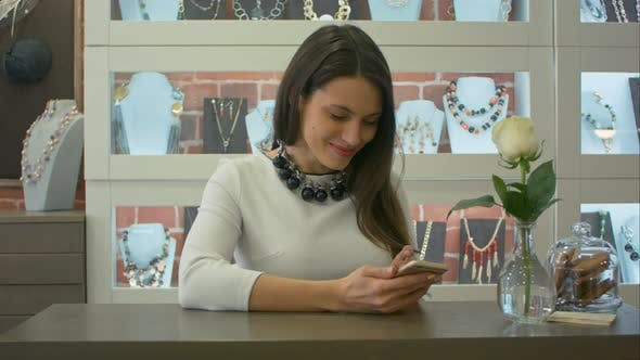Thumbnail for Nice Female Seller Texting Messages on Smartphone and Cute Smiling in a Jewelry Store
