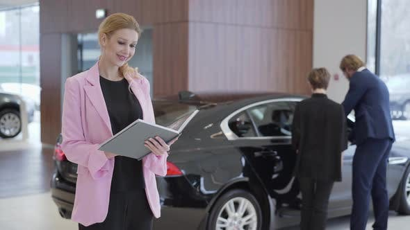 Thumbnail for Portrait of Pleasant Woman in Pink Jacket with a Big Book About Cars in Front of Couple Choosing