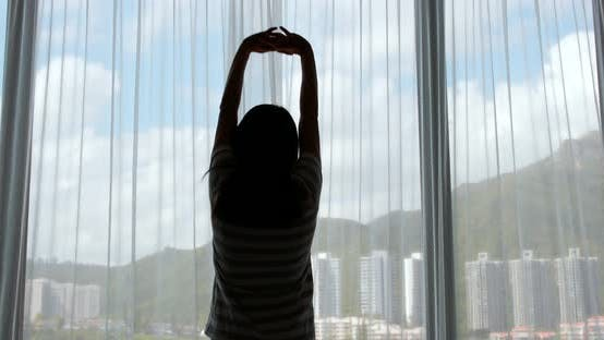 Thumbnail for Woman stretching hand and open the curtain at home