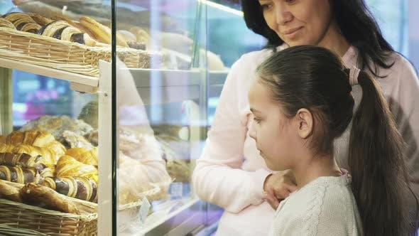 Thumbnail for Adorable Little Girl Choosing Pastry in the Showcase While Shopping with Her Mother