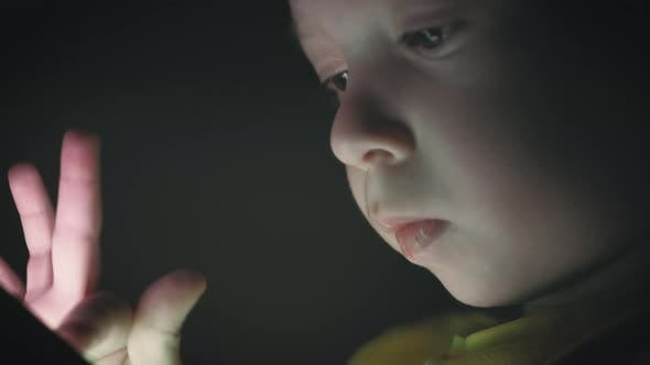 Little Boy, Sitting in a Dark, Playing with Smartphone. Cute Boy Using a Smartphone, Resting on a