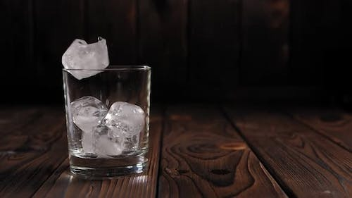 Close-up of Ice Cubes Falling Into an Empty Glass on a Dark Wooden Background.