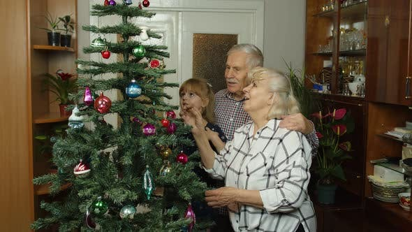 Thumbnail for Kid Girl with Senior Grandmother and Grandfather Decorating Artificial Christmas Tree with Toys