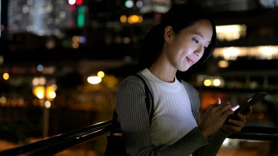 Cover Image for Woman using cellphone in city at night