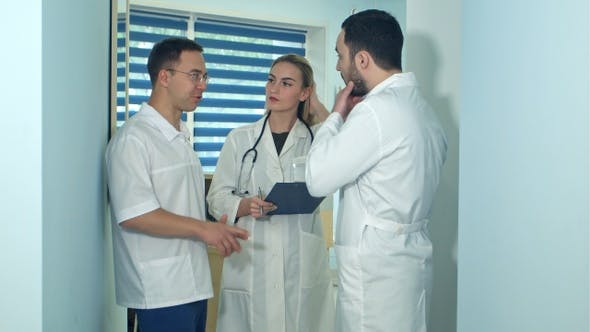 Two Male Doctors Having Discussion While Female Nurse Making Notes