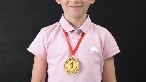 Smiling Schoolboy With First Place Medal Looking at Camera, Diligent Student