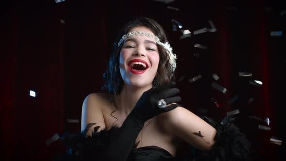 Thumbnail for Retro Styled Woman Dressed in Roaring Twenties Era Smiling Under Confetti Rain on Dark Background