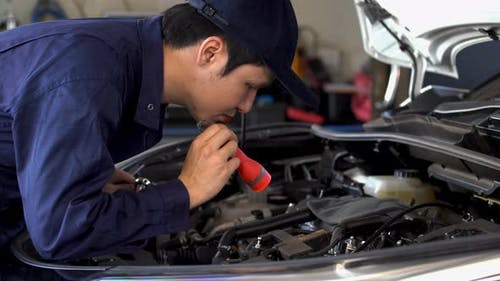 male mechanic holding and shining flashlight to checking a car engine problem