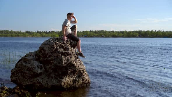 Thumbnail for A Young Man Sits on a Stone By the River and Admires Nature. A Man in Nature.